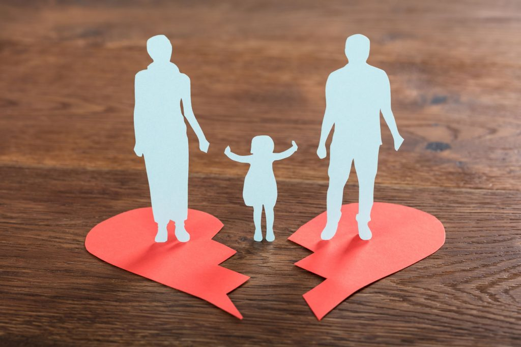 White paper cutouts of woman standing on top of the left side of a red broken heart, man standing on the right side of a red broken heart, with a paper cutout of a child between them
