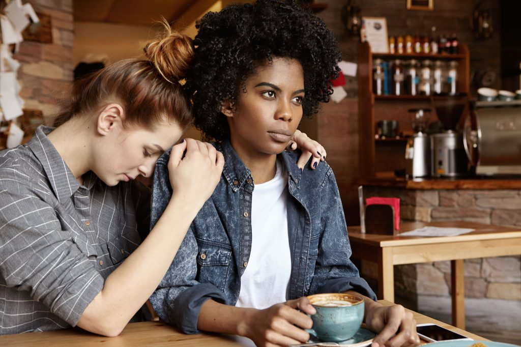 An African woman with an afro is holding a cup of coffee while a white skinned and red headed woman with her hair up in a messy bun holds her with her forehead resting on the African woman's shoulder. The African woman looks off into the distance.