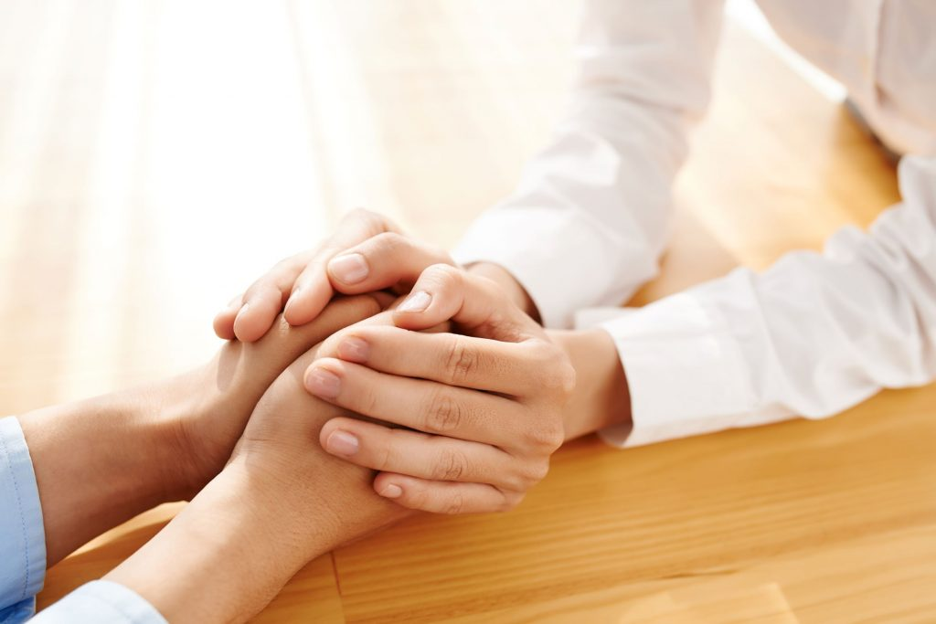 Close up photograph of two white women holding hands across a table.